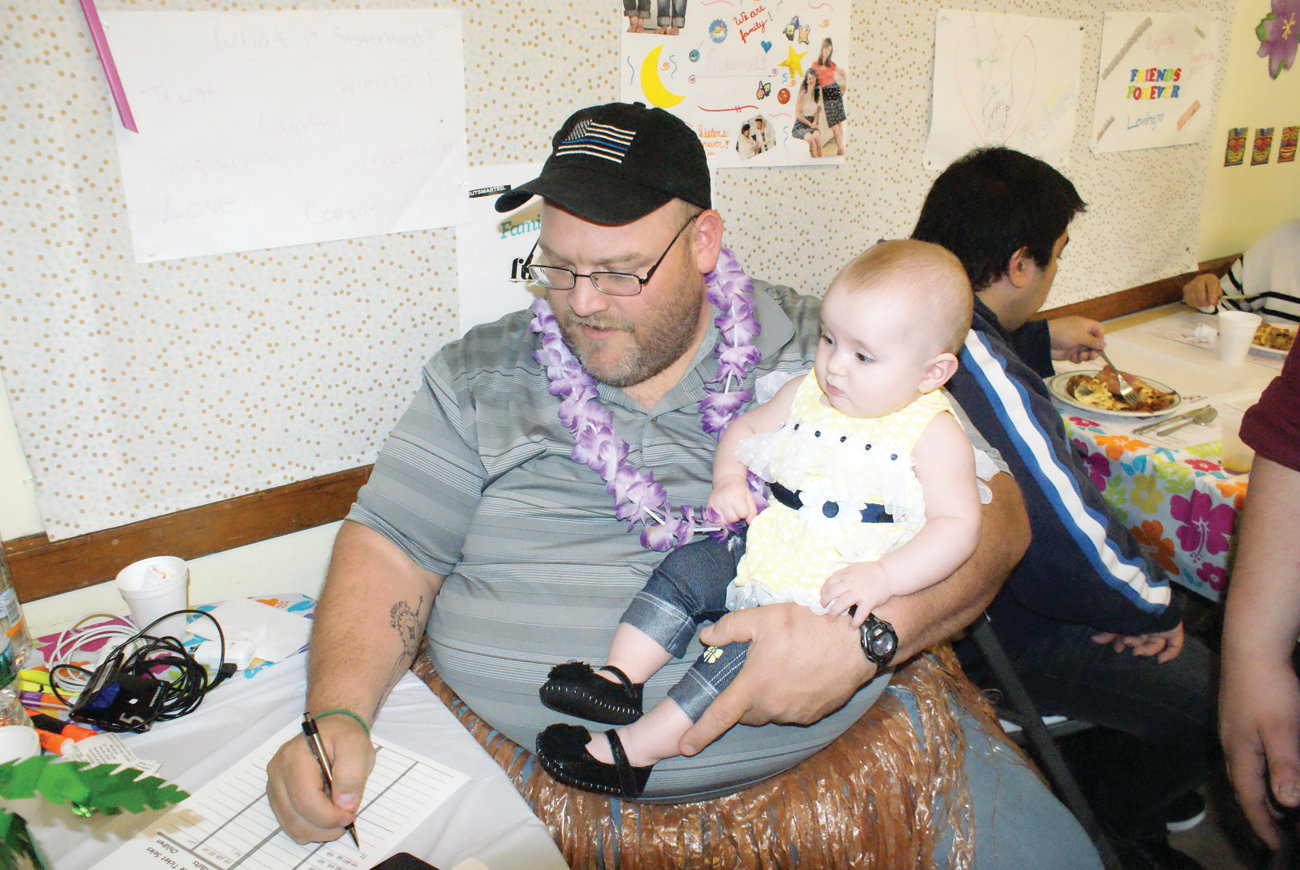 On April 27, Woodridge Congregational Church held its Almost May Breakfast, which has become a longstanding tradition in the community. Pictured holding his granddaughter, Amelia Fortier, is Jay Bombardier who is active in both the church and the Cranston community.