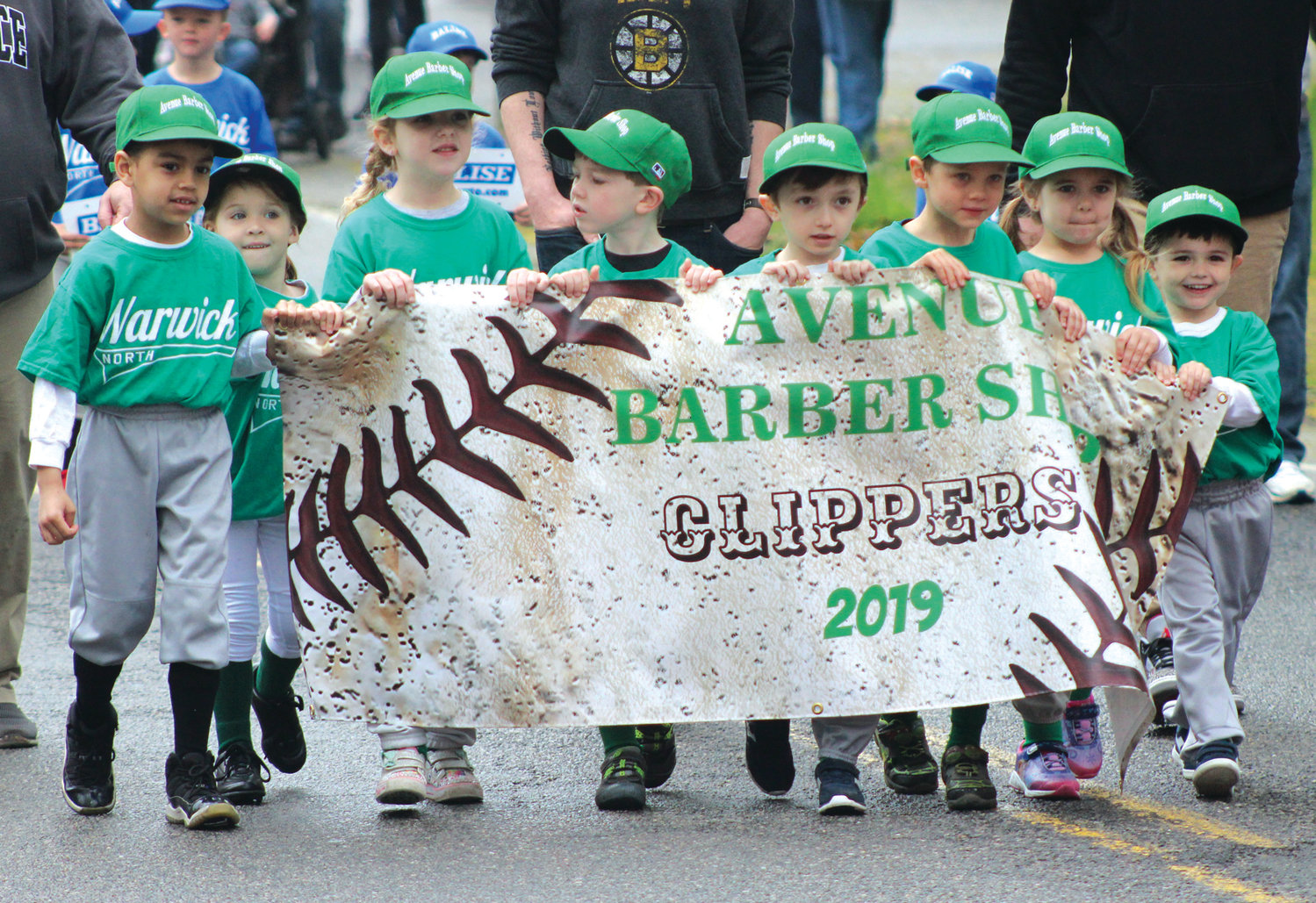 CUTTING THE LINE: Members of the Avenue Barber Shop team from Warwick Little League North lead the way during the annual parade that was held on Saturday morning on Warwick Ave.