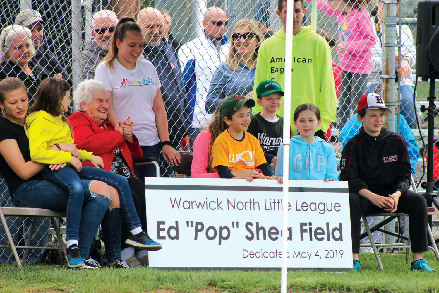 "MAN OF HONOR: The family of the late Ed ""Pop"" Shea accepts the new sign that will be at the Warwick Little League North's minor league field, which was dedicated to his memory on Saturday."