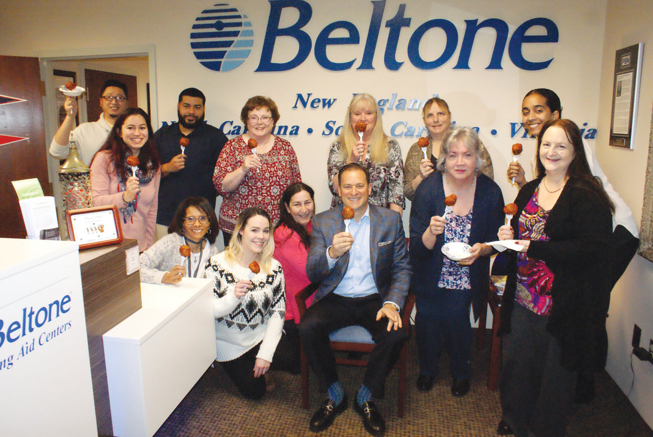 MEATBALL MANIA: Michael Andreozzi, CEO of Beltone New England, seated, is surrounded by the staff at his corporate headquarters in Warwick. Everyone is anxiously waiting to taste his meatballs on a recent Meatball Monday.