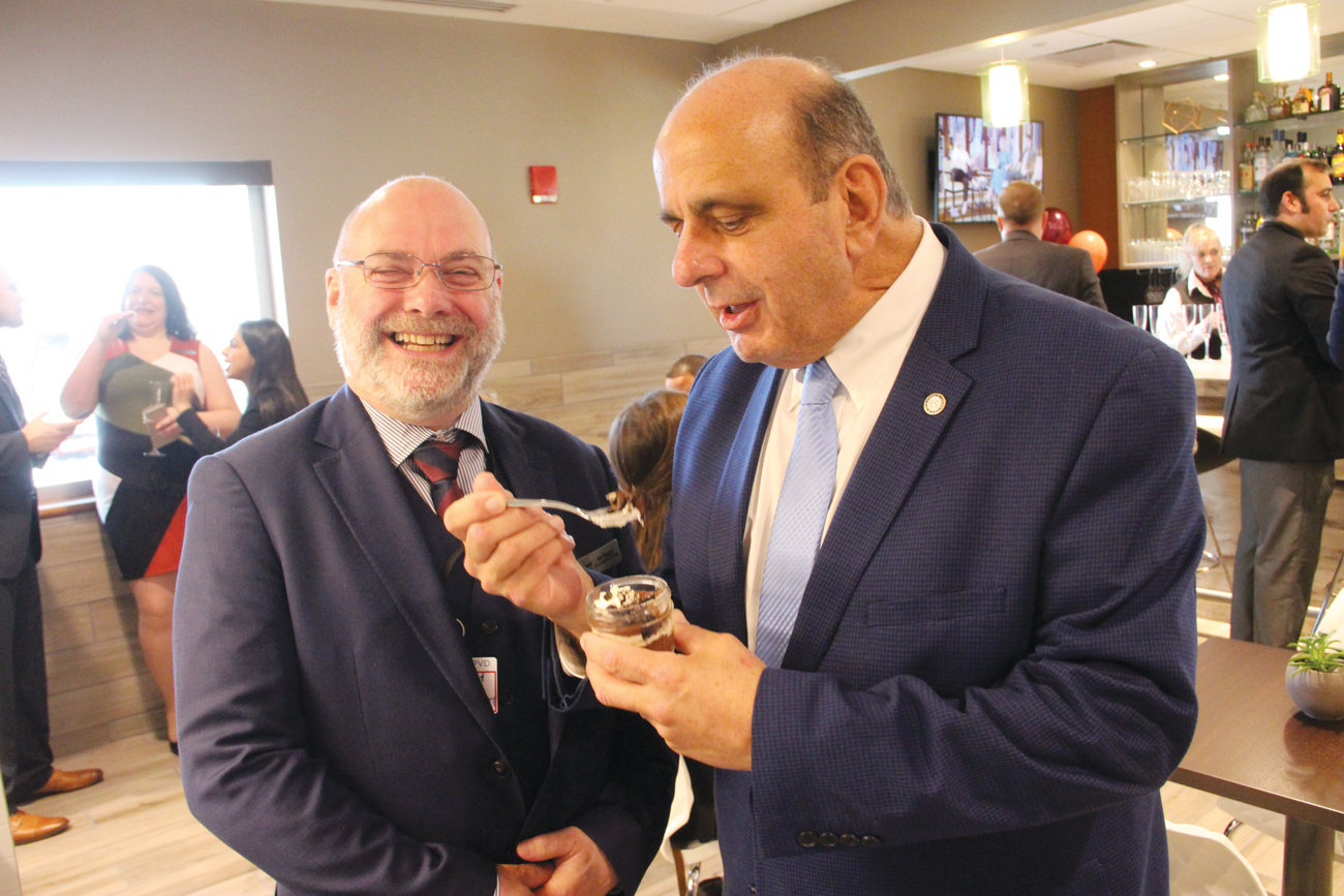 AN OPPORTUNITY TO ESCAPE: Mayor Joseph Solomon enjoys a dessert at the official opening of the Escape Lounge Wednesday at Green Airport. The lounge that is open to the public offers beverages and hot and cold foods prepared on the premise as well as WiFi and private areas for a set price. The price is waived for certain American Express card members. Providing the mayor with all the particulars of the lounge, open from 5 a.m. to 8 p.m., is Sid Higgins, vice president of Escape Lounges.