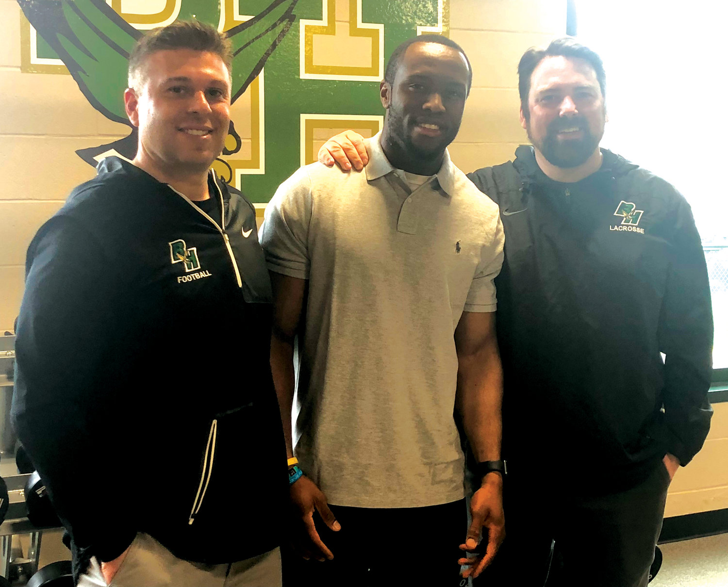 ARIZONA BOUND: Lee Moses (center) visits members of the Bishop Hendricken coaching staff prior to his departure to Arizona for NFL rookie minicamp this weekend.