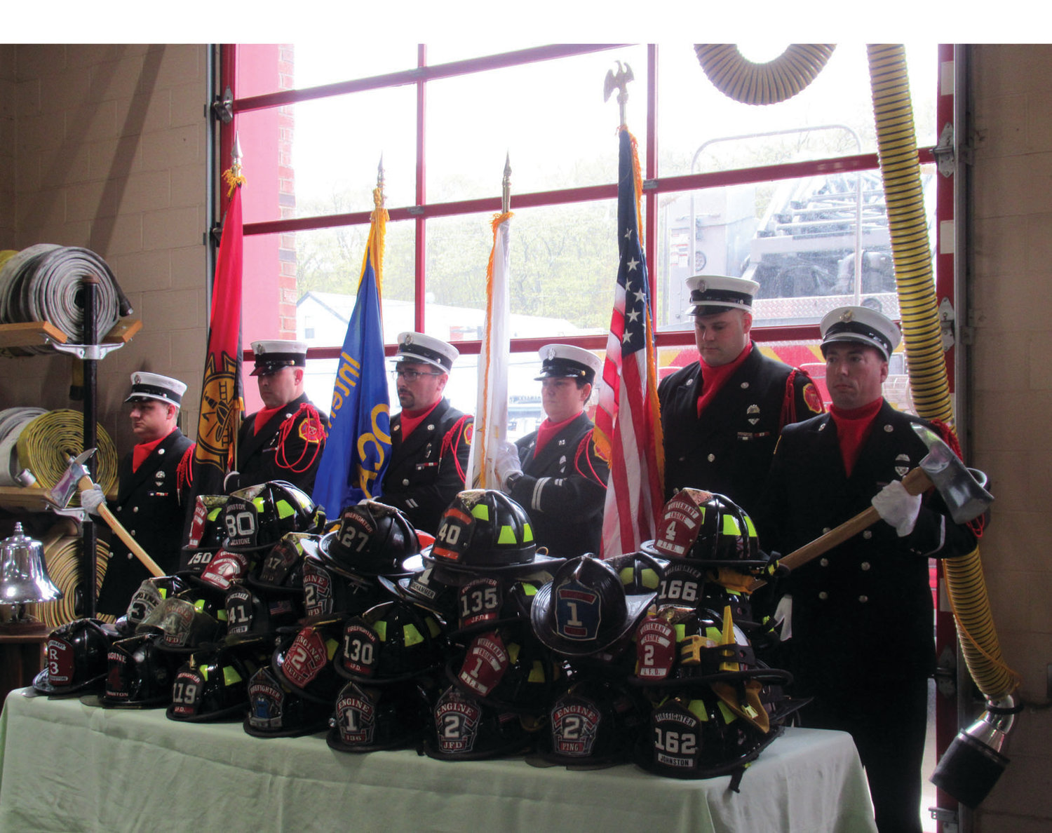 GRAND GUARD: The Johnston Fire Honor Guard stands behind the helmets of all current firefighters as the Rev. Ryan J. Simas, the department's chaplain, performs the Blessing of Helmets during Sunday's memorial ceremony.
