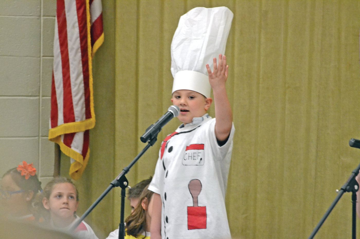 BON APPETIT: Hoxsie first-grader Shaun Moranto portrays a chef during his performance.