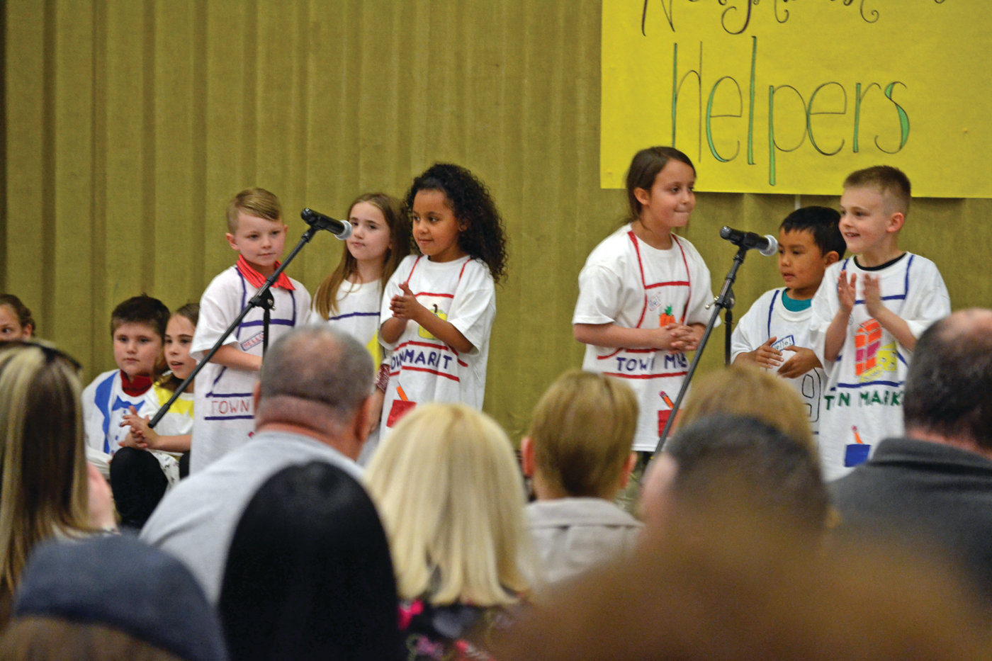 GOOD APPLES: Hoxsie first grade students, left to right, Adam James, Destiny Griffin, Maiya Gonzalez, Alicia Nichols, Jacob Kue and Brayden Arnold, portray grocery store workers in their song.
