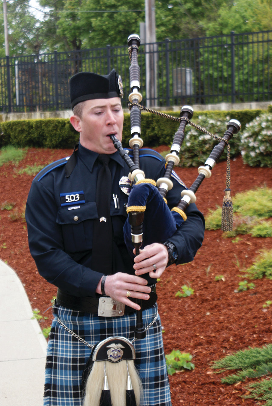 "SOMBER SOUNDS: Officer Patrick McCoy performs ""Amazing Grace"" on the bagpipes during the memorial ceremony."