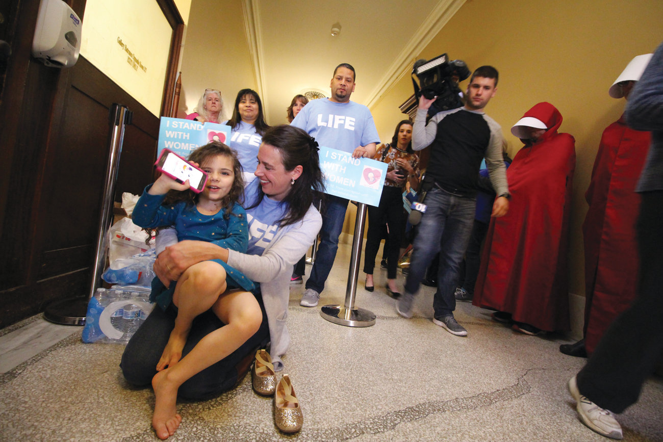 CAMPED OUTSIDE THE COMMITTEE: Pro-life advocate Kara Young brought along her daughter Mary to join the hundreds lined outside the Senate Judiciary Committee for Tuesday's meeting.