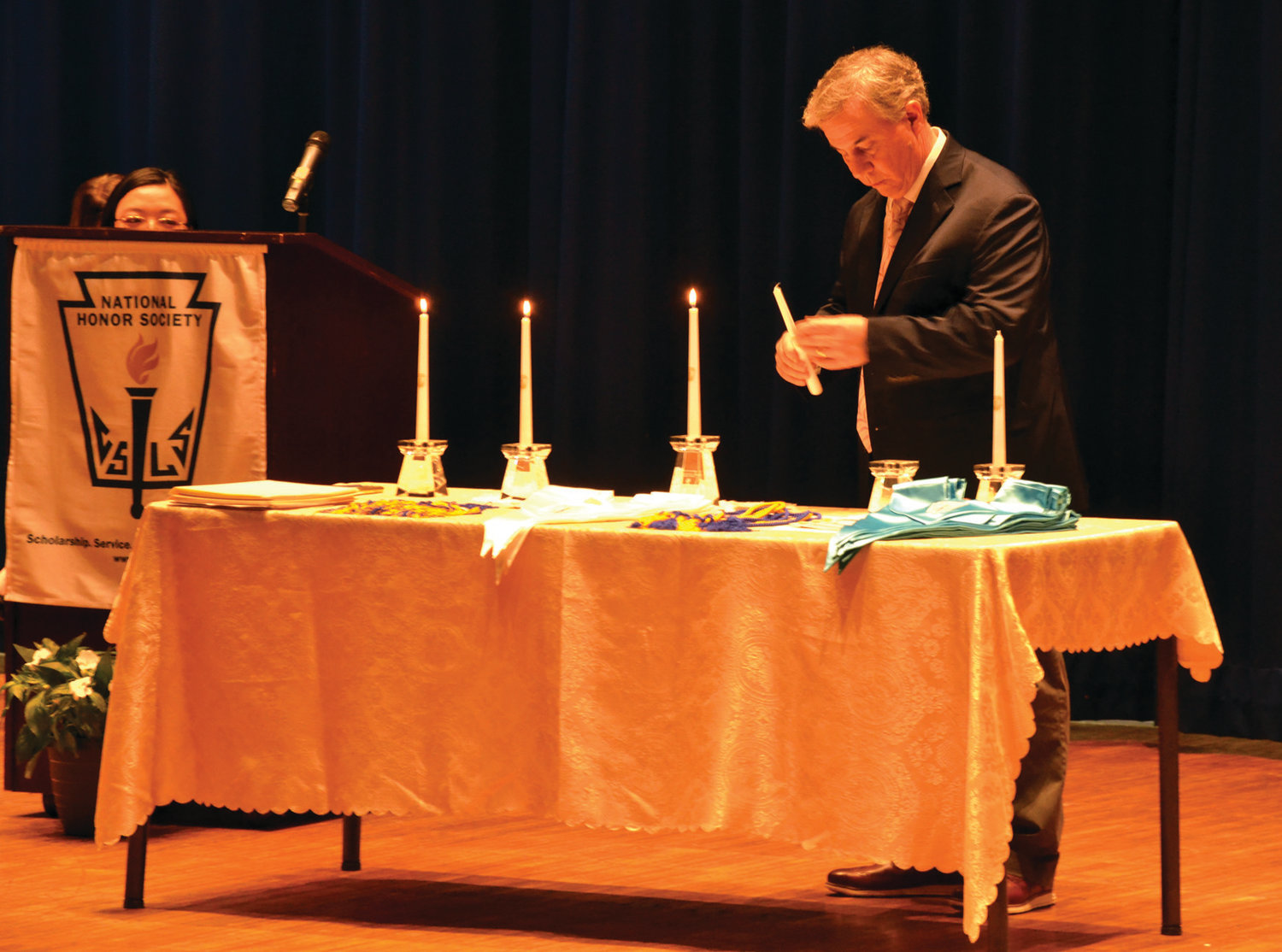 A NIGHT TO REMEMBER: History teacher Stephen Donovan lights a candle before speaking. A candle was lit for each core tenet of the National Honor Society -- character, scholarship, leadership and service