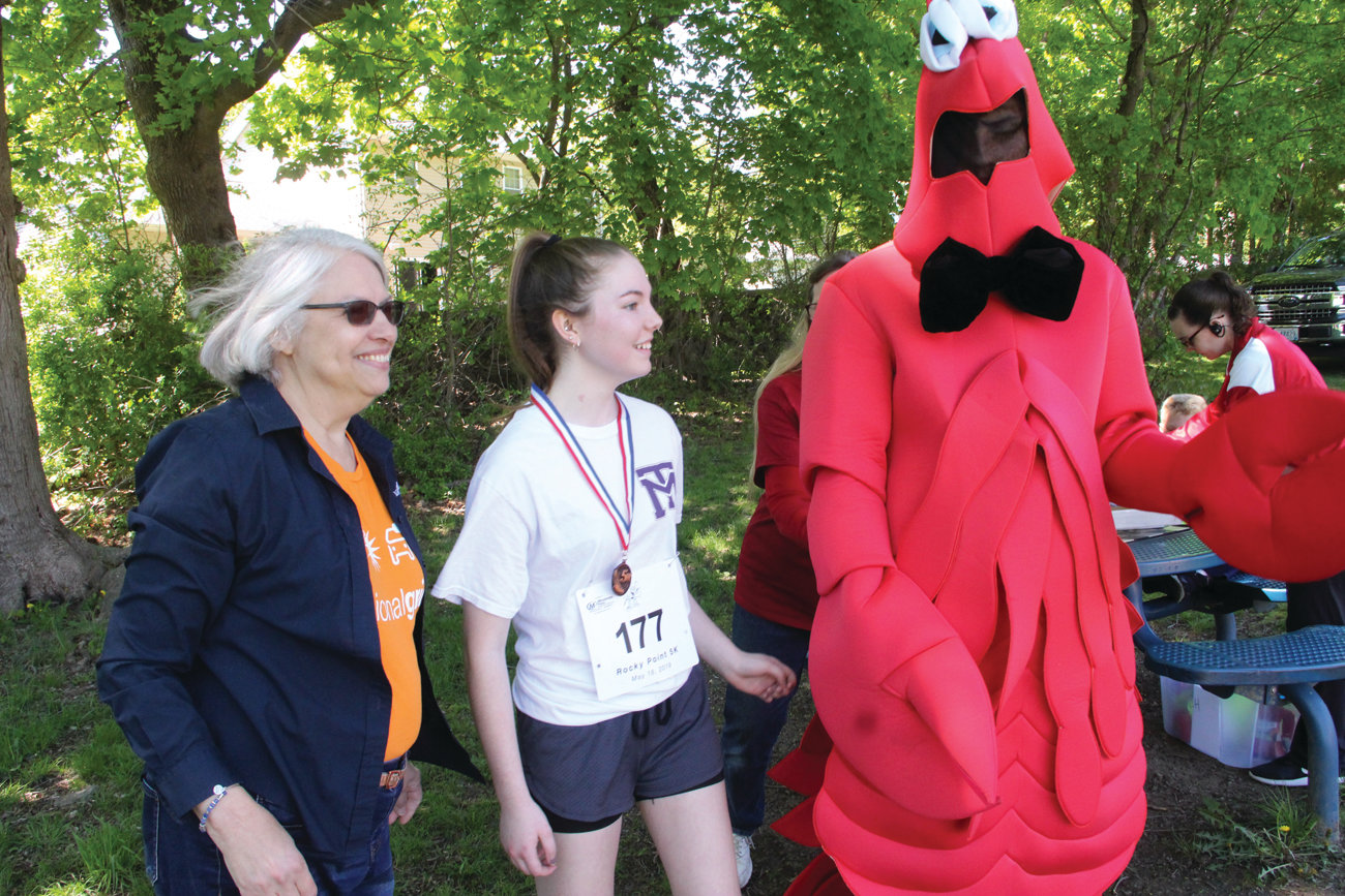 LOBSTER RECOGNITION: The top three finishers in each of the categories were presented a medal and got to pose with the mascot for the race after, of course, a claw shake. Here Catherine Faucher, who placed third in the girls' division, prepares for her photo.