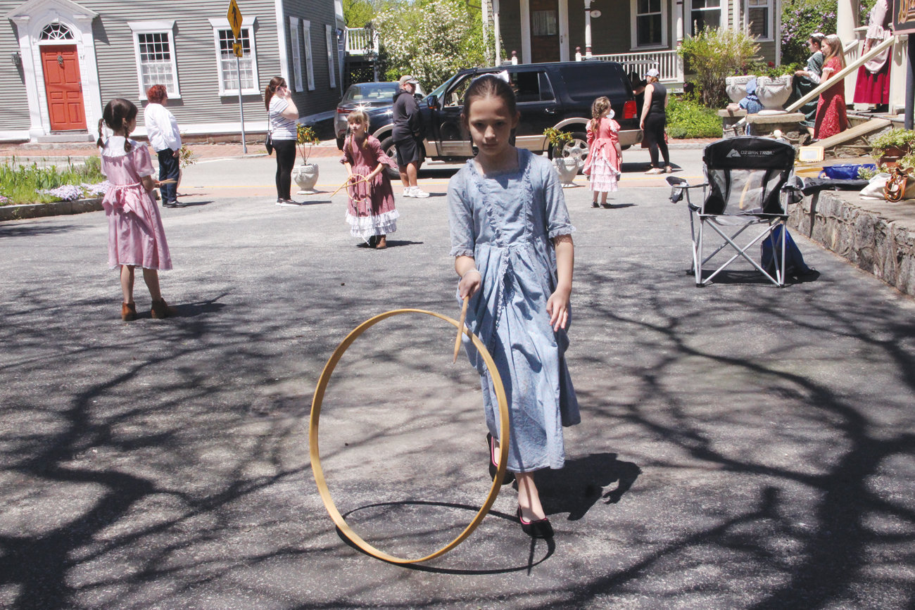 ROLLING ALONG: Stephanie Henner got the hang of rolling a hoop as she and others played the roles of students at a colonial school.