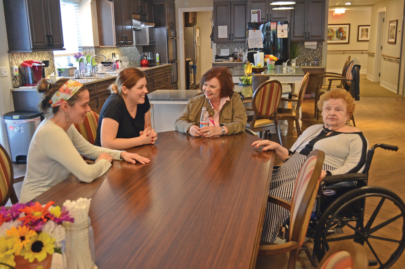 FAMILY ENVIRONMENT: Saint Elizabeth Green House home guide Sarah Bowater (left), Chrissy Yuras, Cheryl Prior and Green House home resident Claire Hill chat at the dinner table of one of Saint Elizabeth Community's Green House homes.