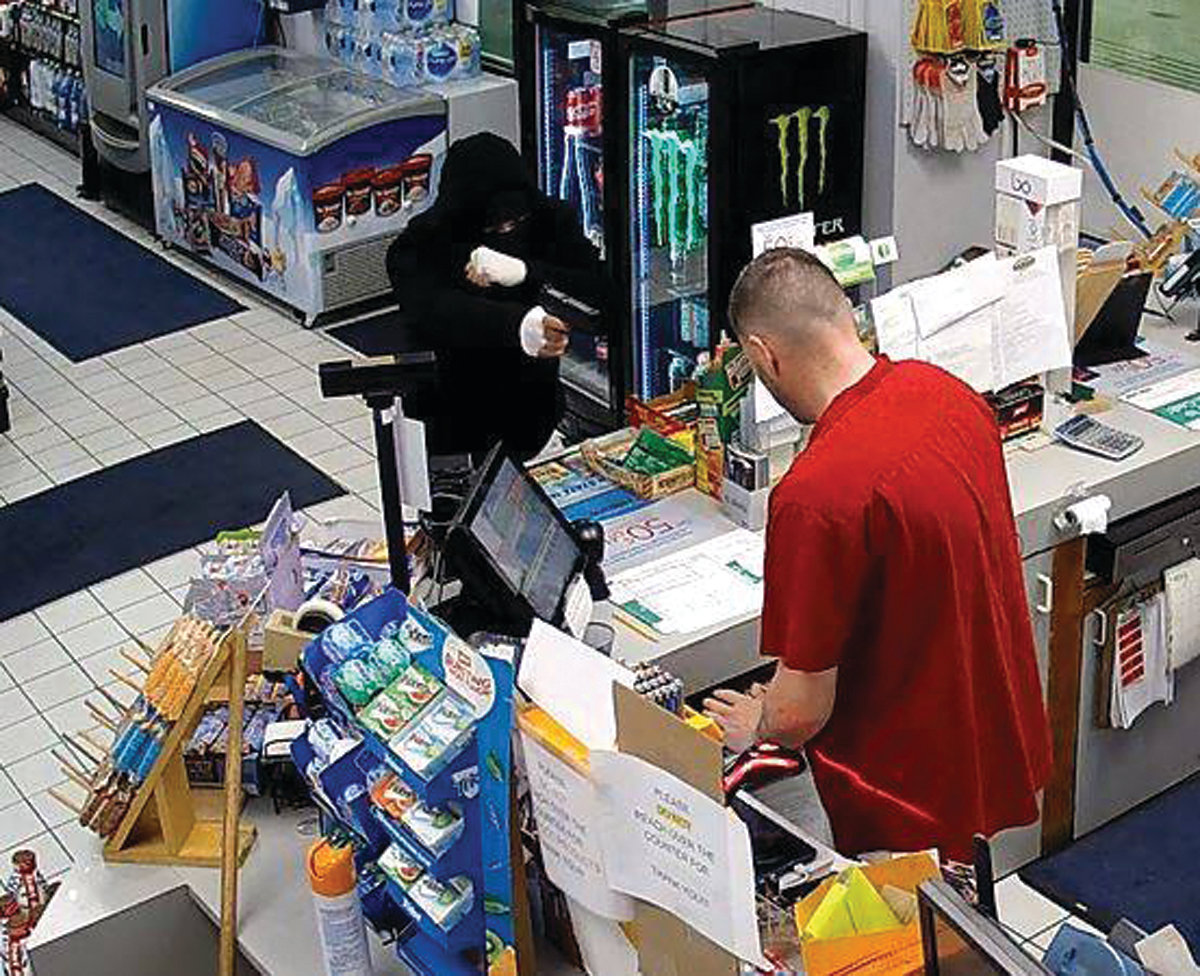 ARMED ROBBERY: This image taken from surveillance footage shows a suspect in a recent robbery at the Mobil gas station on Elmwood Avenue pointing a firearm at a clerk.