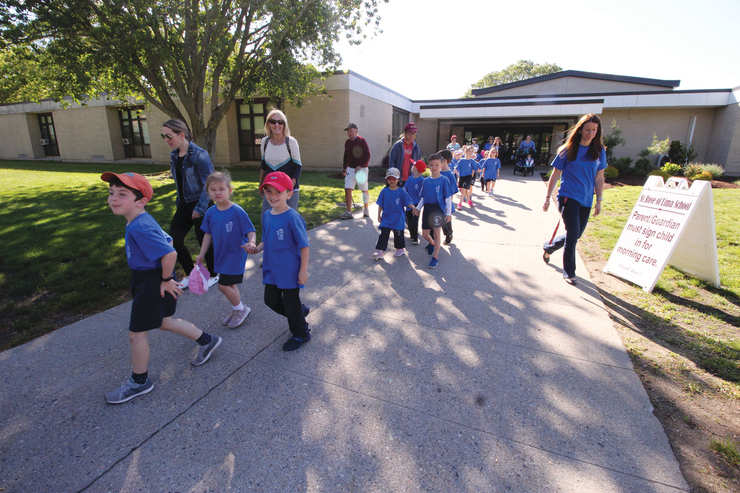 BUSTING OUT OF SCHOOL: Preschoolers and lower grade students took to the sunshine and warm and windy conditions for their walk around the block to benefit St. Rose of Lima School.