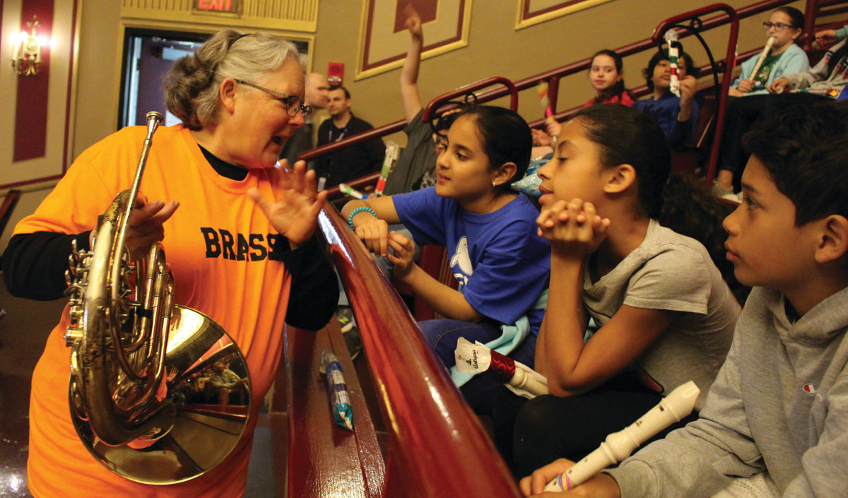 LINKING UP: (from left) Amelia Baez, Jayla Shepard and Ariel Ochoa, students at Eden Park Elementary School in Cranston, learn about the French horn from Orchestra member Elizabeth Hayes.