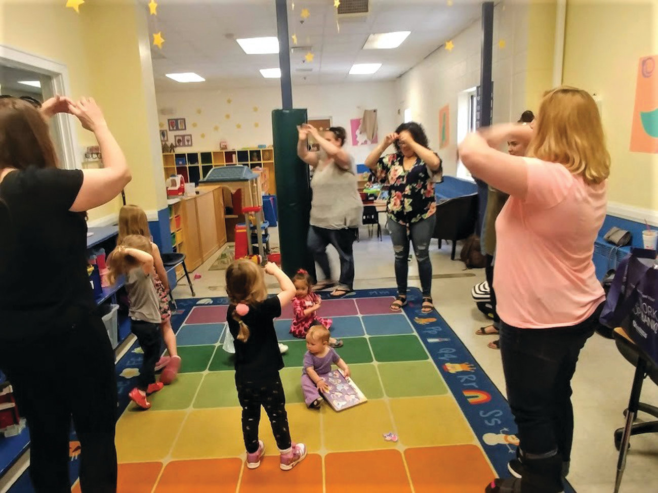 "A FREE PLAYGROUP: Theresa McFarlane and Cherie Cruz lead the children and their caregivers in ""The Itsy Bitsy Spider"" before beginning their program, which focused on wind, parades and Memorial Day."