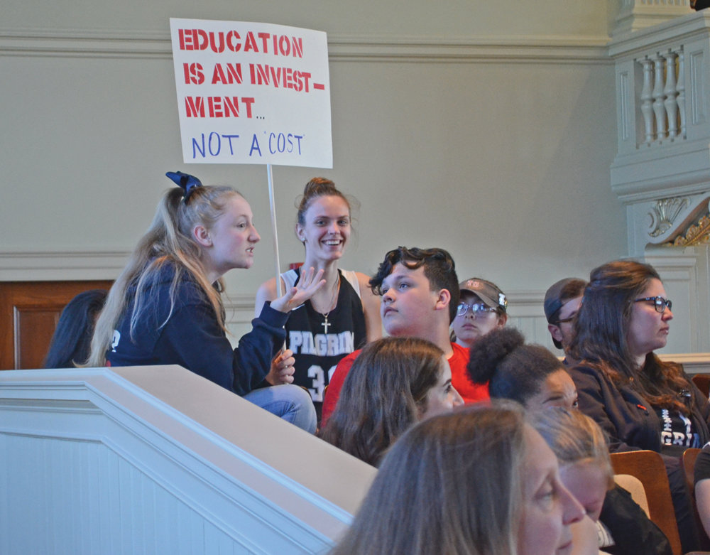 AN INVESTMENT: A student holds up a protest sign at the Monday night meeting of the Warwick City Council.