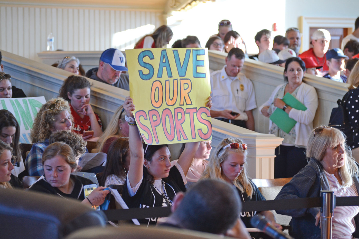 "SAVE THE SPORTS: A Pilgrim High School student athlete encompasses the student position with a sign reading ""Save Our Sports"""