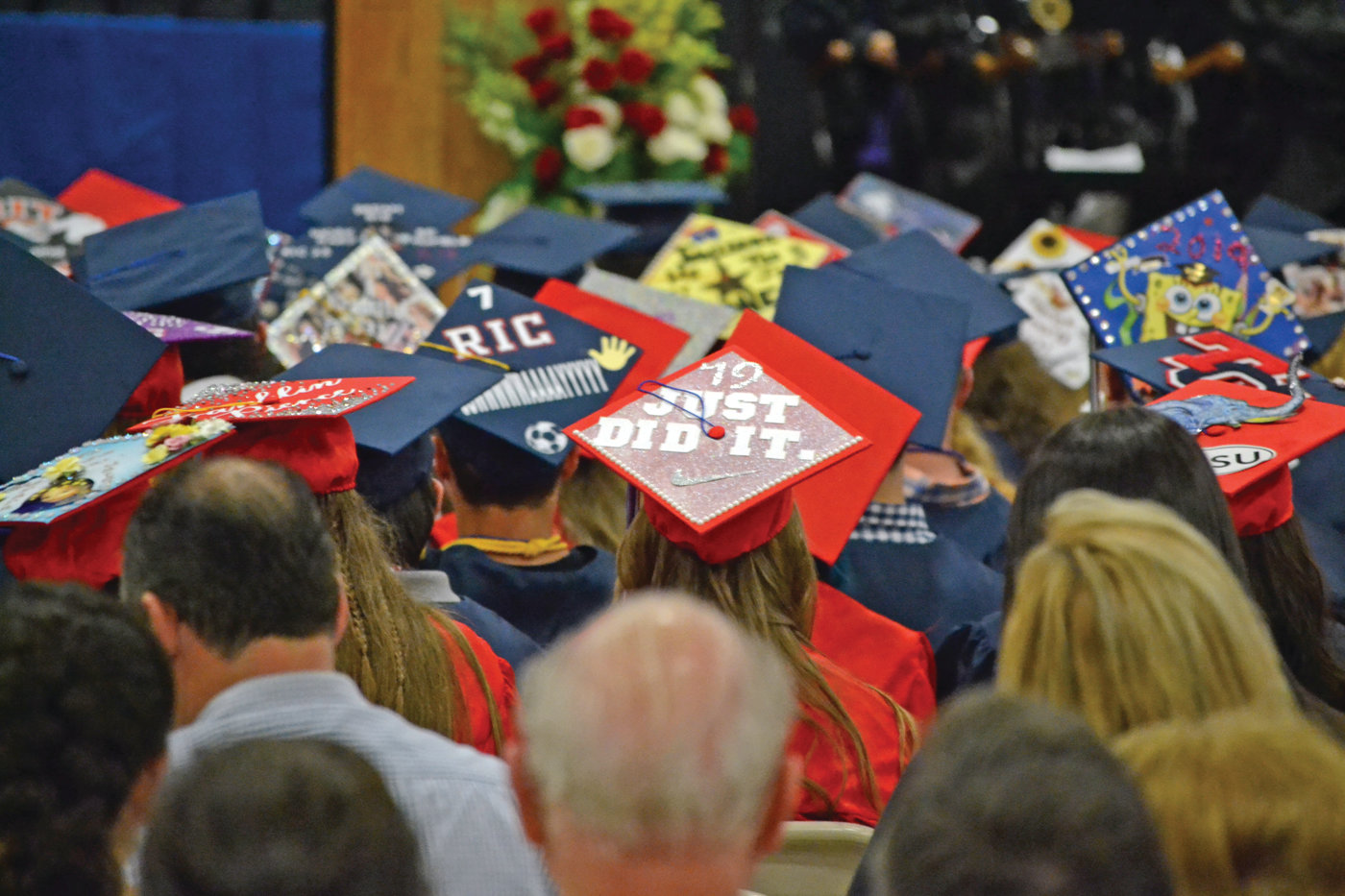 "TIP OF THE CAP: Plenty of students participated in the graduation tradition of decorating their caps. One lampooned the famous Nike slogan, while another celebrated its wearer's unique hairstyles throughout the years, reading ""Life's too short to have boring hair."""