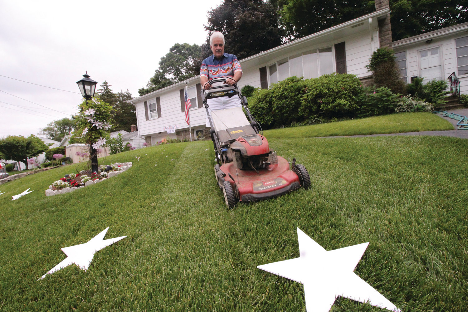 "A CUT ABOVE THE REST: Lou ""Paz"" Pazienza cuts a stripe as part of his Flag Day display on Woodview Drive."