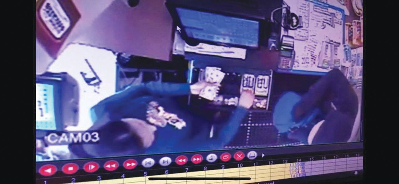 ROBBED AT KNIFEPOINT: This image taken from surveillance video shows a suspect, right, ordering a clerk to take money from a register during an armed robbery at the Gulf Express in Pawtuxet Village on Tuesday afternoon.