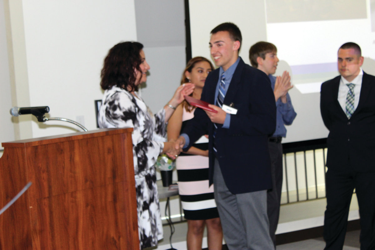 THE BIG MOMENT: Graduate Tom Marcello proudly receives his Project SEARCH diploma from Superintendent Jeannine Nota-Masse.