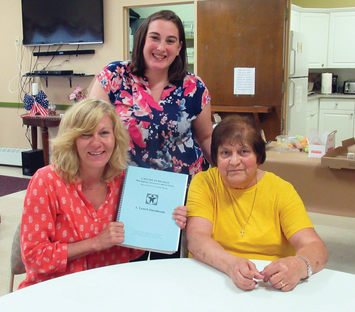 TEACHER TANDEM: Jessica Lemieux, standing, resident services coordinator for the Johnston Housing Authority, joins special volunteer lecturers Amy Bragger, left, and Geri Lebeau at last Thursday's ceremony at Pell Manor.
