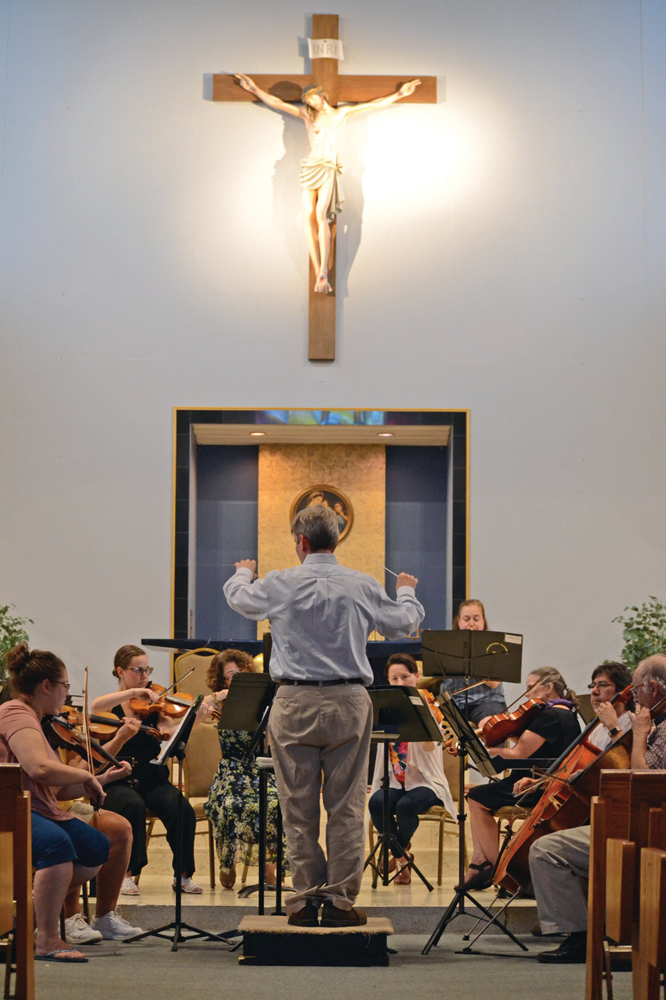 GRAND STAGE: Dr. Brian Cardany leads the orchestra, set up along the front altar of St. Kevin Church. The acoustics within the church were something music fanatics would appreciate.