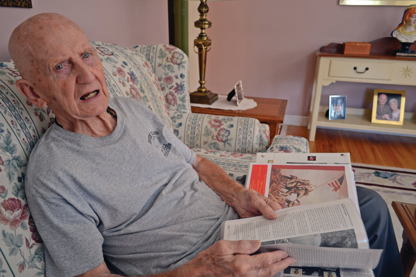 ARCHIVIST: Ray Raiche has accumulated enough historical information and photographs to fill 22 albums. He leafs through one here while sitting on his couch in his Warwick home.