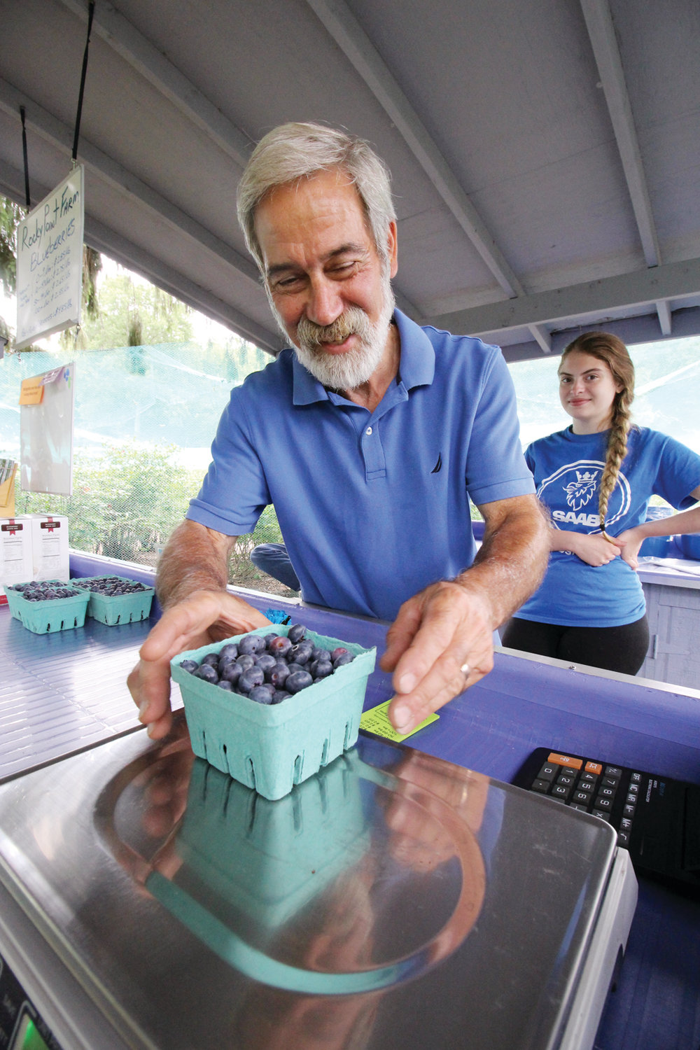 POUND-BY-POUND: Joe Gouveia weighs up a pound of the juicy berries. Working the sand with him is Kendra Manchester, a student at CCRI who aims to become a registered nurse.
