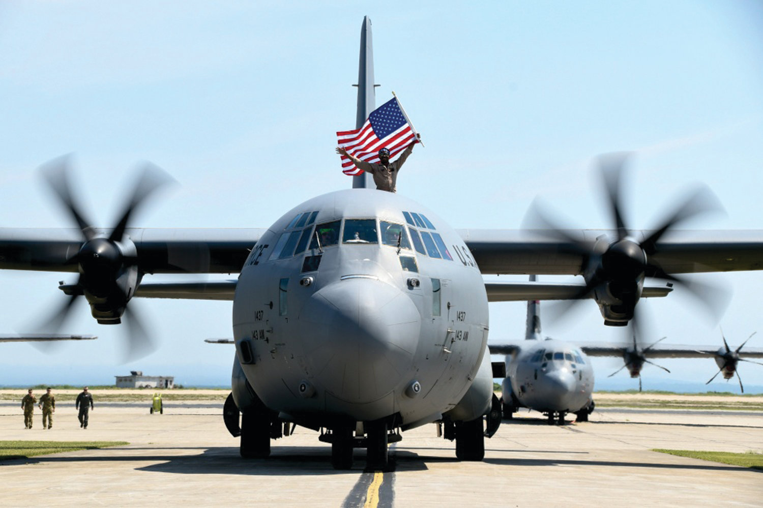 NICE RIDE: An Airman waves from one of the C-310J aircraft during the celebration at Quonset on July 5.