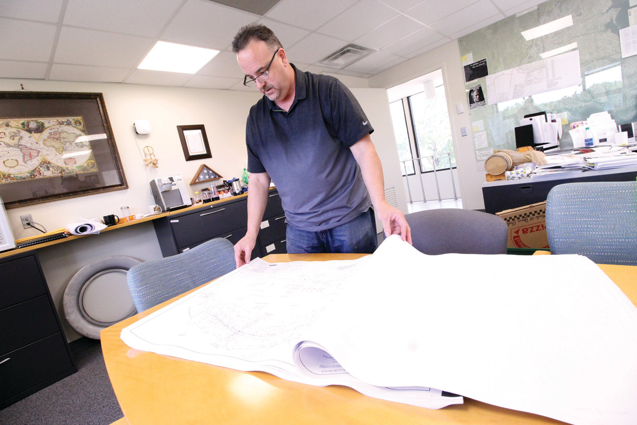 BEST LAID PLANS: Earl Bond, project manager for the Warwick Sewer Authority, looks over draft plans for the Bayside sewer project, which at the moment is up in the air.