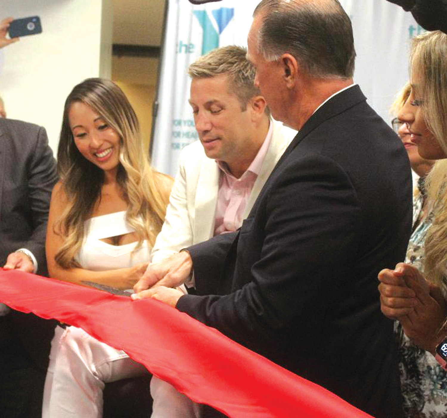 "OPEN FOR BUSINESS: Gary ""Tiger"" Balletto (center) along with family and members of the Cranston YMCA, cut the ribbon to open the state's new and only adaptive gym facility. Balletto, a Providence native and former professional boxer, suffered a spinal cord injury in 2013 and has been working toward helping others with similar injuries."