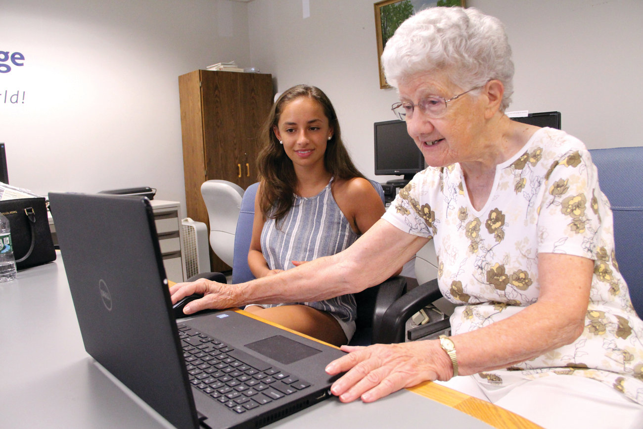 TEACHER AND STUDENT: URI pharmacy student Qiana Ferraro helps Marie George retrieve her email. Marie has mastered how to Skype her two younger sisters who live in the Washington, D.C. area.
