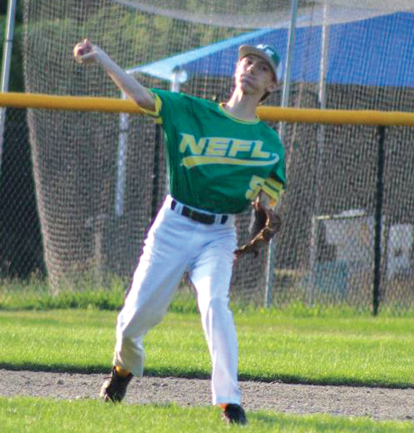 HOT CORNER: NEFL's Andrew Merryfield makes the throw to first from third base in Woonsocket.