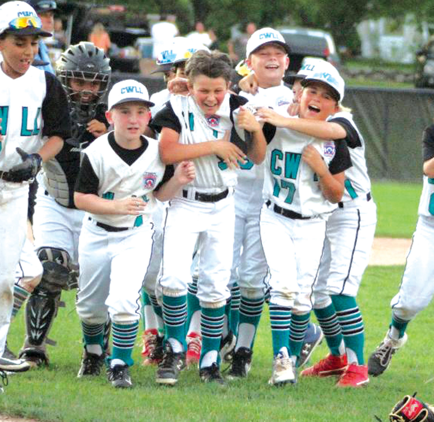 PARTY TIME: Members of the CWLL 10's rush the field after winning the state championship.