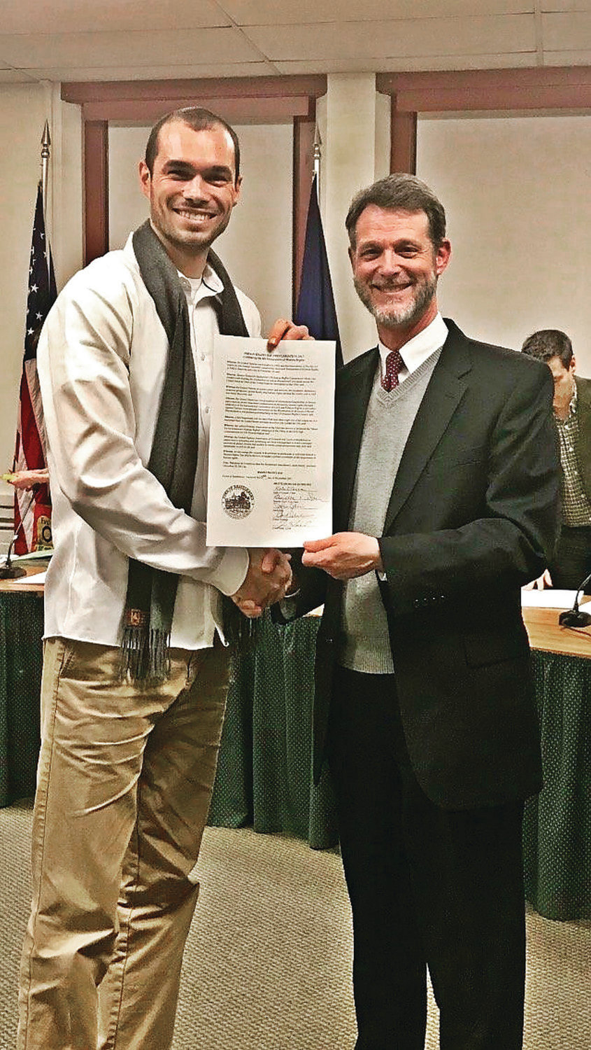 Justin Bibee, left, and Peter Elwell, town manager of Brattleboro, Vermont, hold a proclamation declaring Human Rights Day in this 2017 photo.
