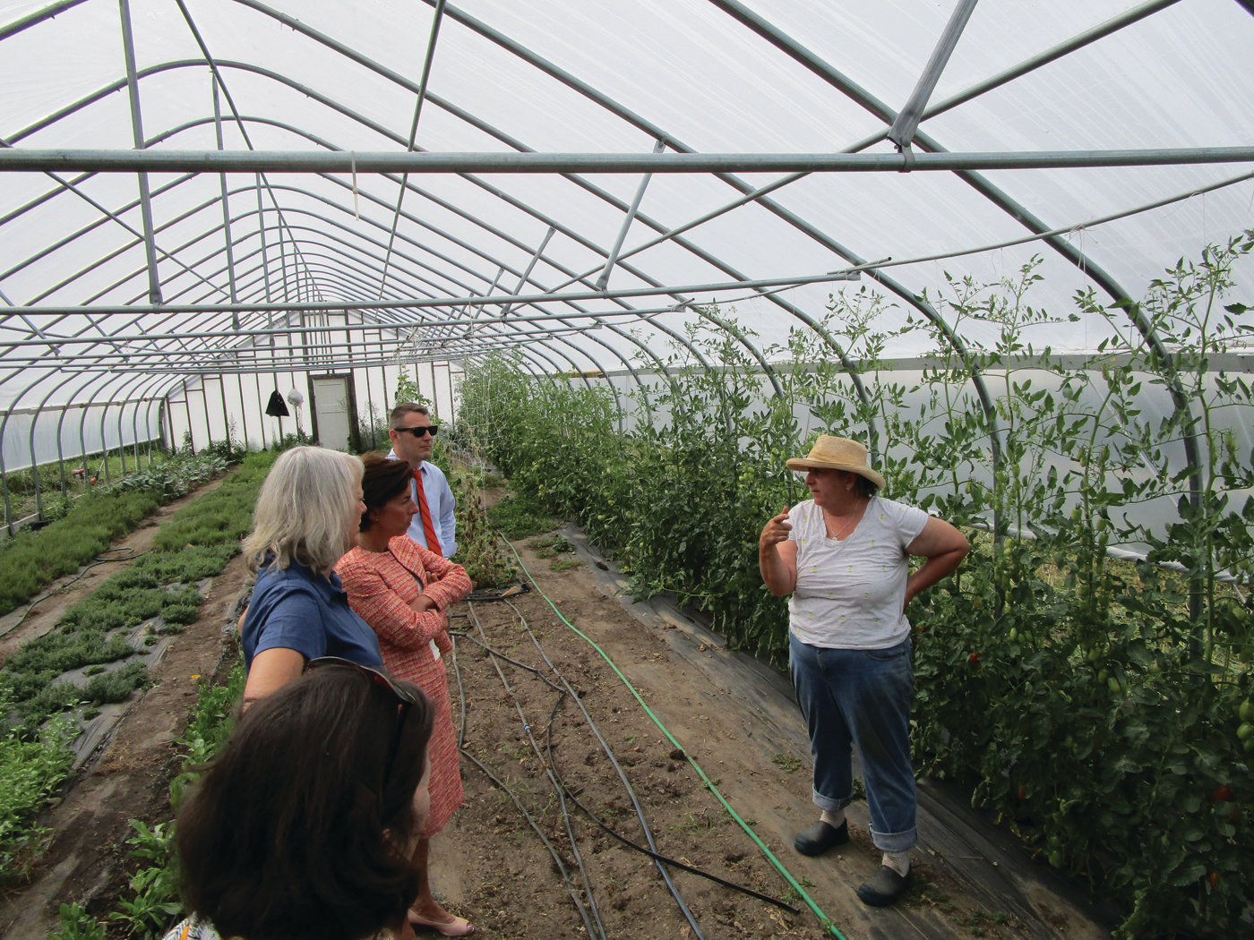 IN THE GREENHOUSE: Christina Dedora of Blue Skys Farm, right, speaks with DEM Director Janet Coit, left, and Gov. Gina Raimondo during Tuesday's visit.
