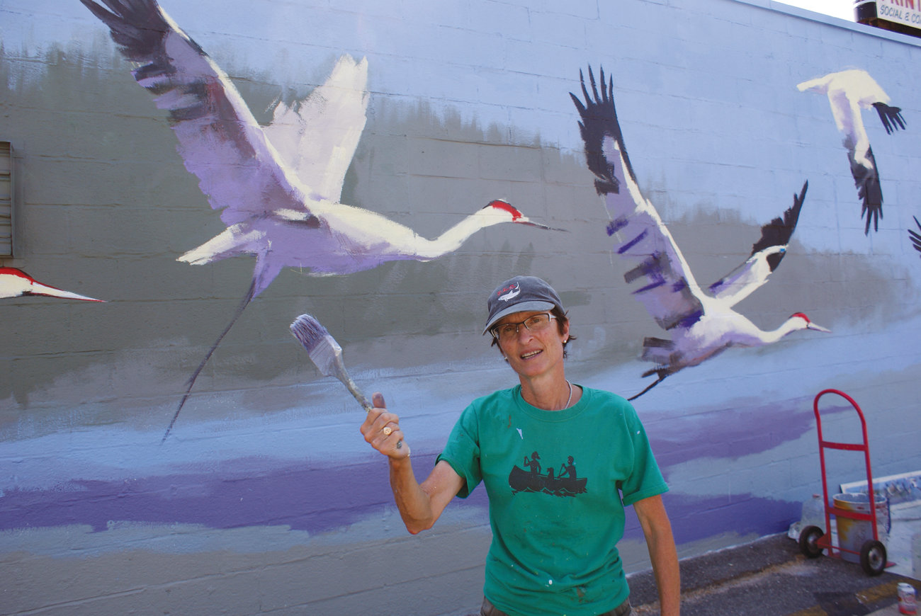 "TAKING FLIGHT: Amy Bartlett Wright posted near her mural titled ""Crane Flight"" on the outside wall of Crosstown Press in this August photo."