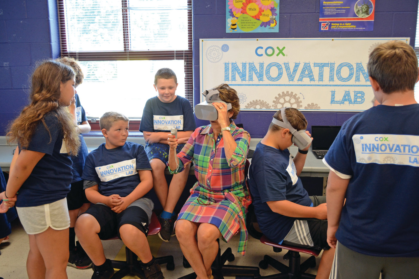 WHERE IS SHE? Debra Cornish, vice president of human resources for Cox Communications, takes a VR headset for a whirl, getting some help from Boys and Girl Club members.