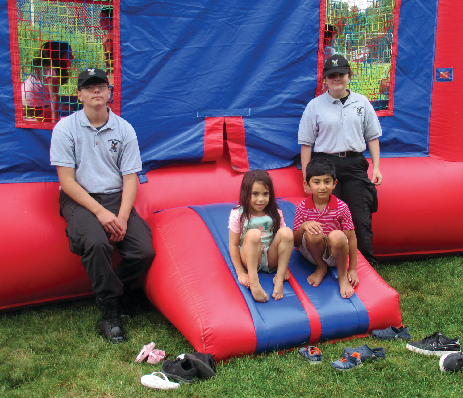SPECIAL SAFETY: Explorers Devin Medeiros, left, and Kayla Desrosiers keep a watchful eye on Aliyah Ethier, 5, and Rayaan Buch, 6, who enjoyed this bounce house supplied by My Cousin Vinny's during the National Night Out celebration.