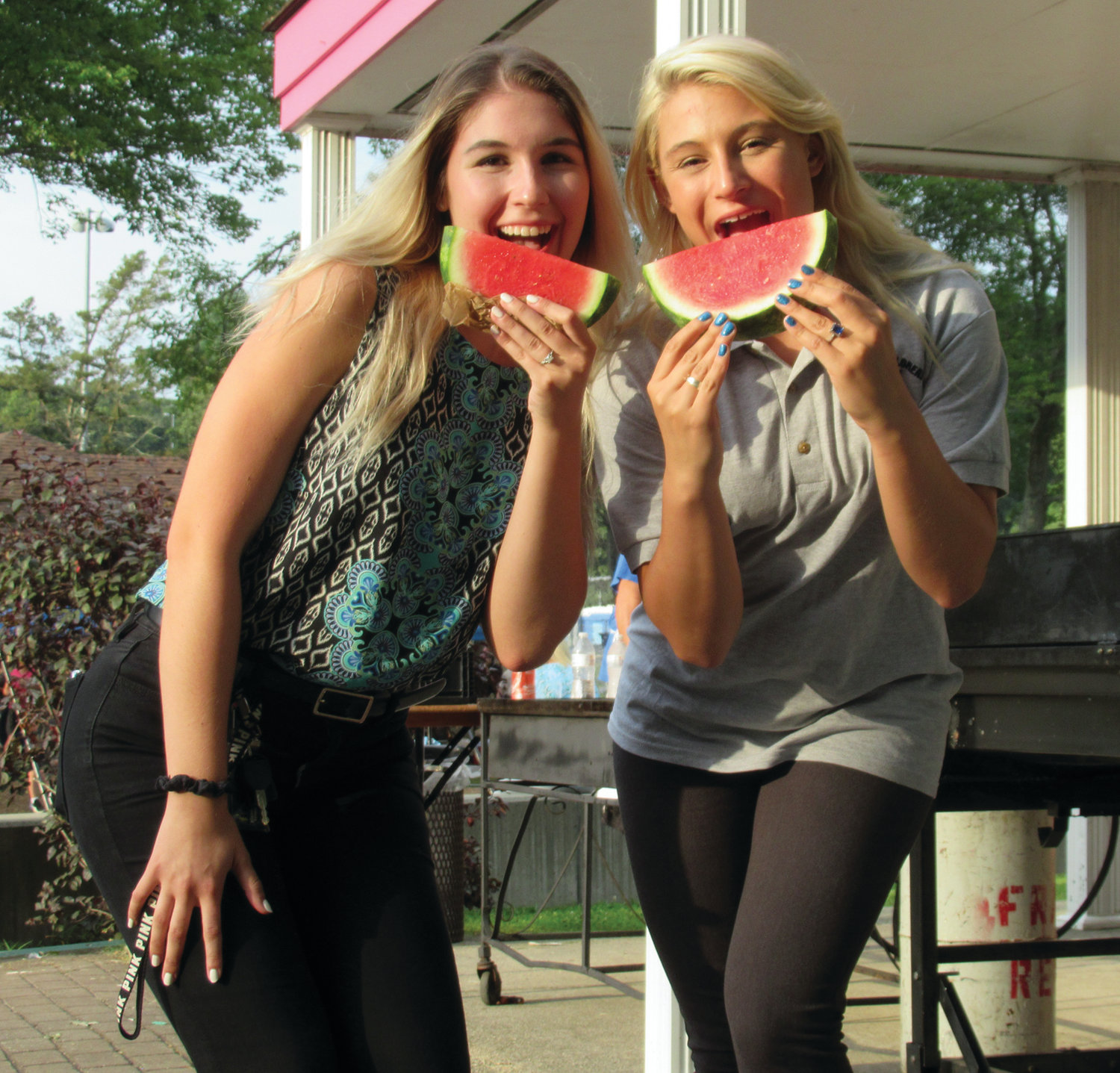 DELIGHTFUL DUTY: Explorer Post advisors Antoinette Bongiornos of Smithfield, left, and Allegra Graziano of Johnston are about to sample a piece of the chilled watermelon that was sliced and served Tuesday's night.
