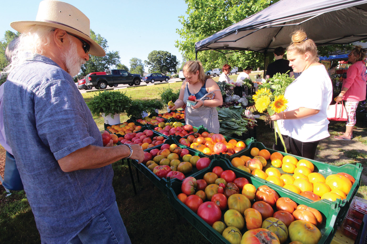 GRAPEFRUITS? The size and color of some of the tomatoes at the stand operated by Christina Dedora of Blue Skys Farm could have some shoppers wondering if they were oranges and grapefruits. There will be a tomato tasting and raffle at the market this Saturday.