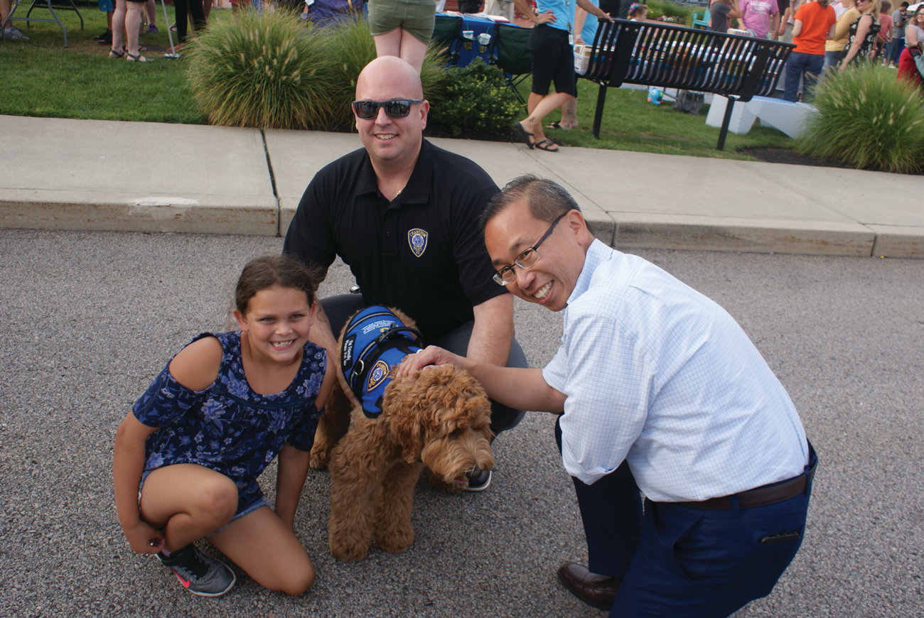 K-9 CALI: Mayor Allan Fung helps Madison Cavanaugh of Cranston meet the Cranston Police Department's Special Victims Unit K-9 Cali and Detective Mike Iacone during National Night Out.