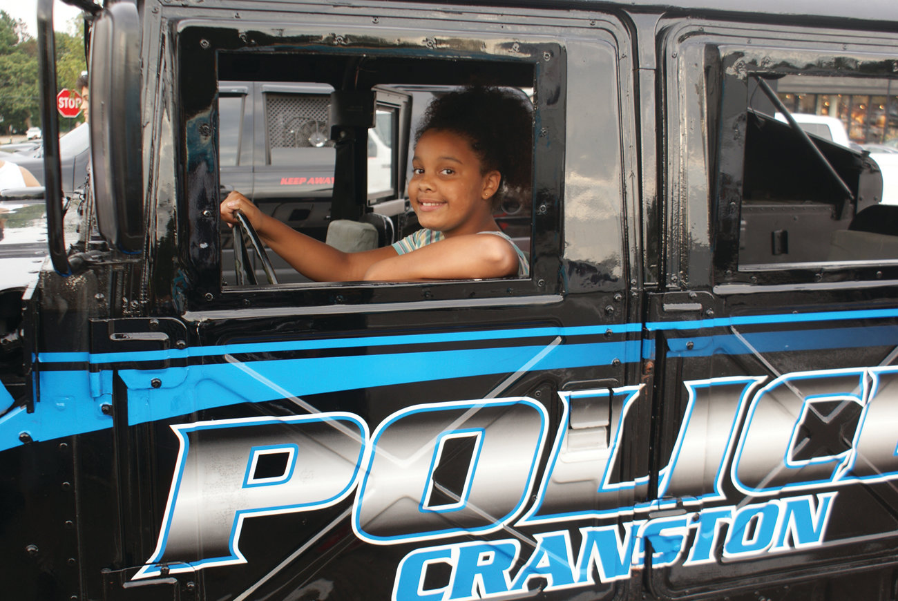 ENJOYING THE VIEW: Sitting high in a Cranston Police vehicle was Caylie Savage, 10, during National Night Out.