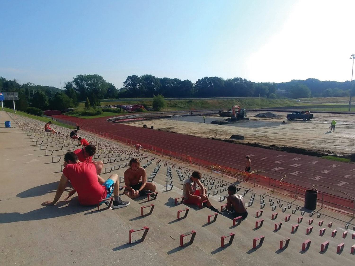 HARD AT WORK: Despite the near-100 degree heat and early morning hours, members of the Cranston High School West football team were hard at work on the cement stairs in the bleacher area of the school's renovated athletic complex in this August photo.