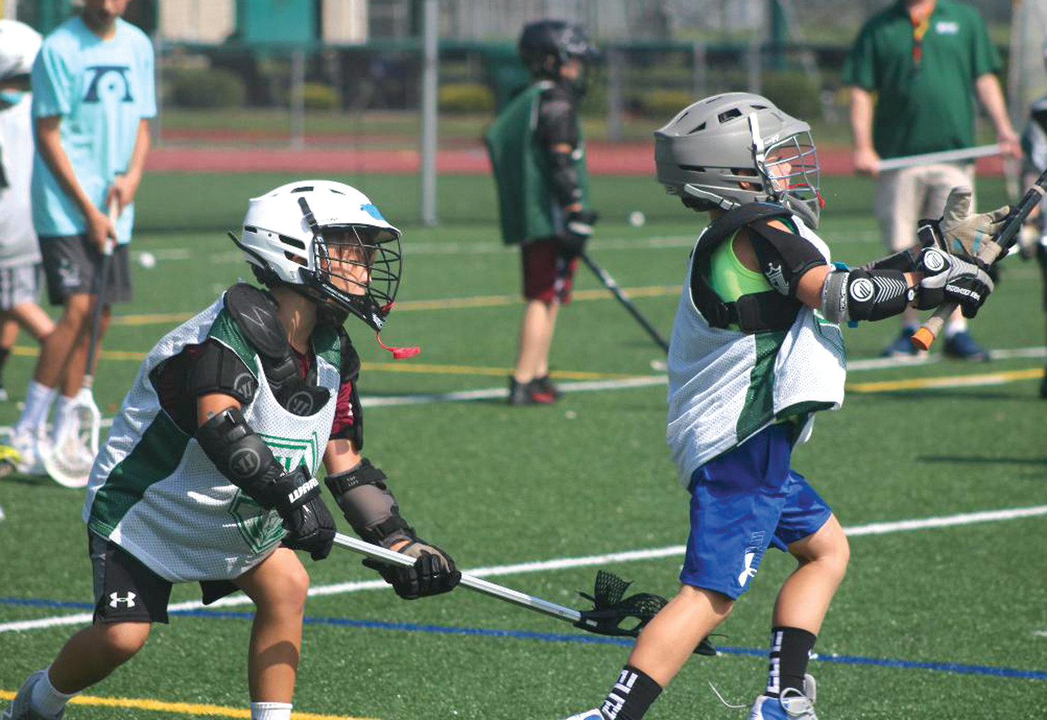 HAPPY CAMPERS: Local lacrosse players run through drills at Hendricken's Hawks Academy camp at the school earlier this week.
