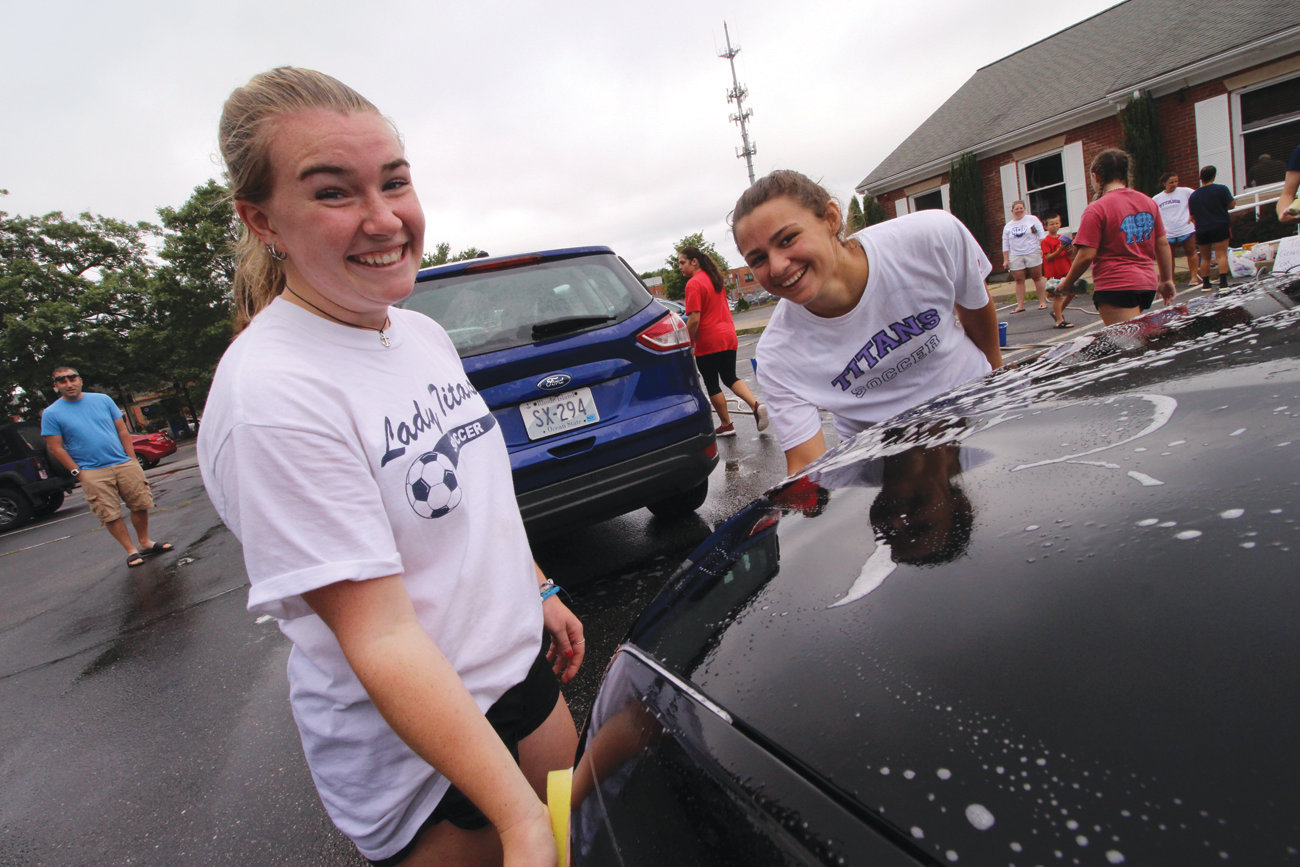 HOW'S IT DONE: Co-captains Erin O'Toole and Cassie Cirella put some muscle into cleaning one of the scores of vehicles the team washed Saturday.