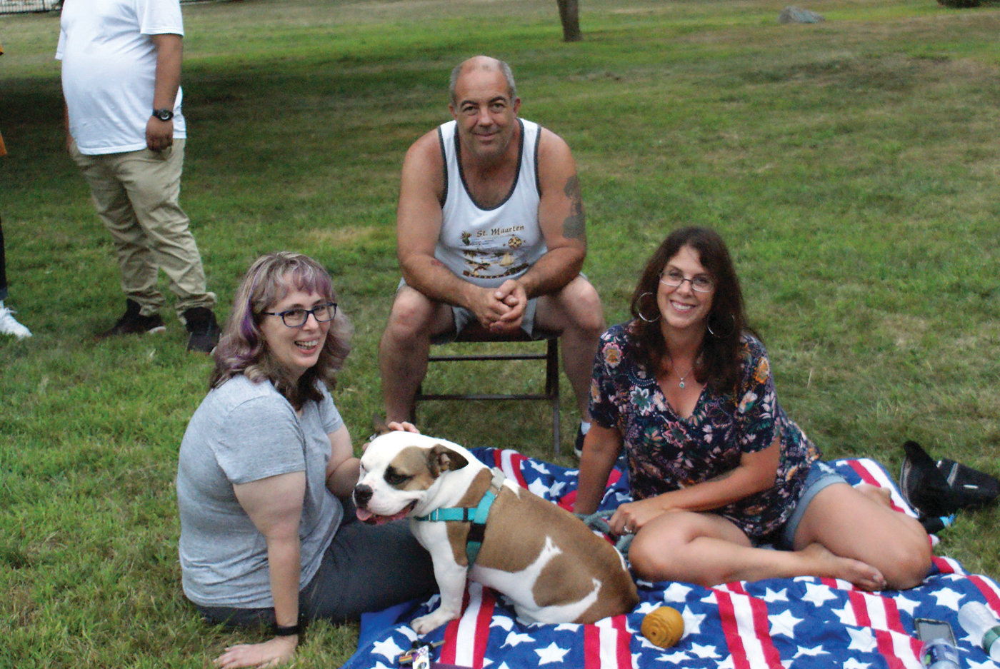 FRIENDS AND FAMILY: Enjoying some time with Mike, a roughly 4-year-old rescue and therapy dog who is an English bulldog/pitbull mix, are Tracy Murphy and his owners, Gary and Michelle Rose.