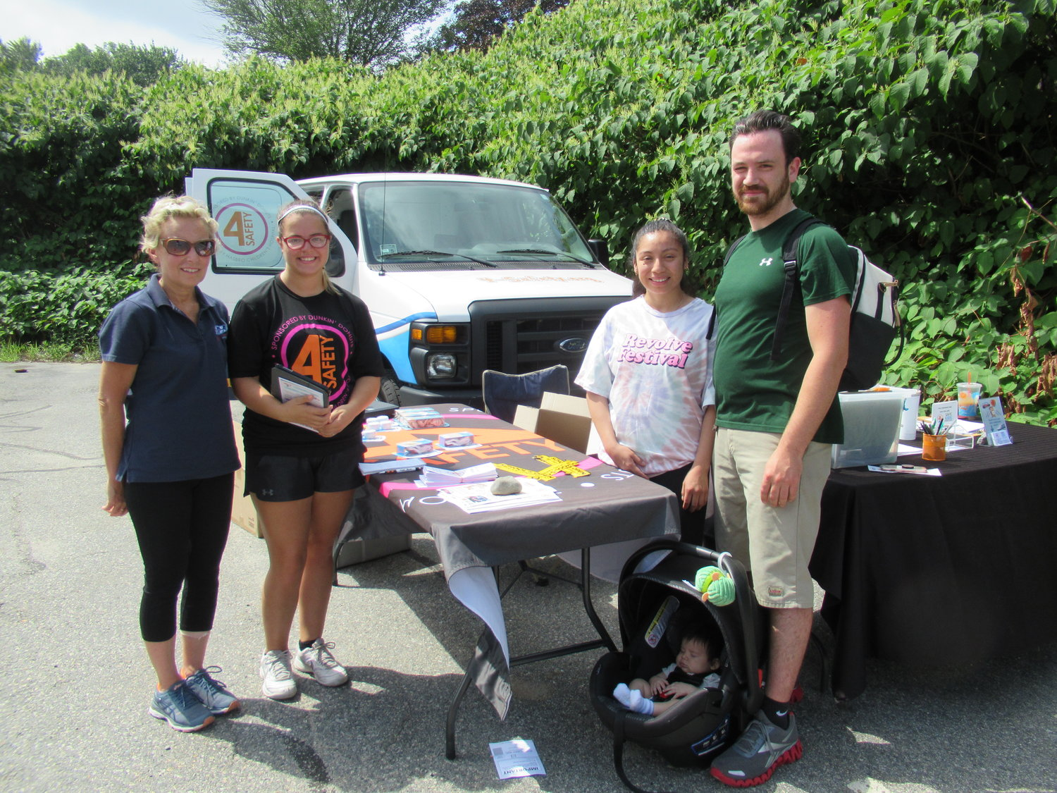 SPECIAL SAFETY: Couples like Michael McLynch and Jennifer Dela Cruz found the Tri-County Community Action Agency's first-ever farmers market the perfect spot to learn about child seat safety from Hasbro Children's Hospital staffers Dina Burstein and Leah Kiernan.