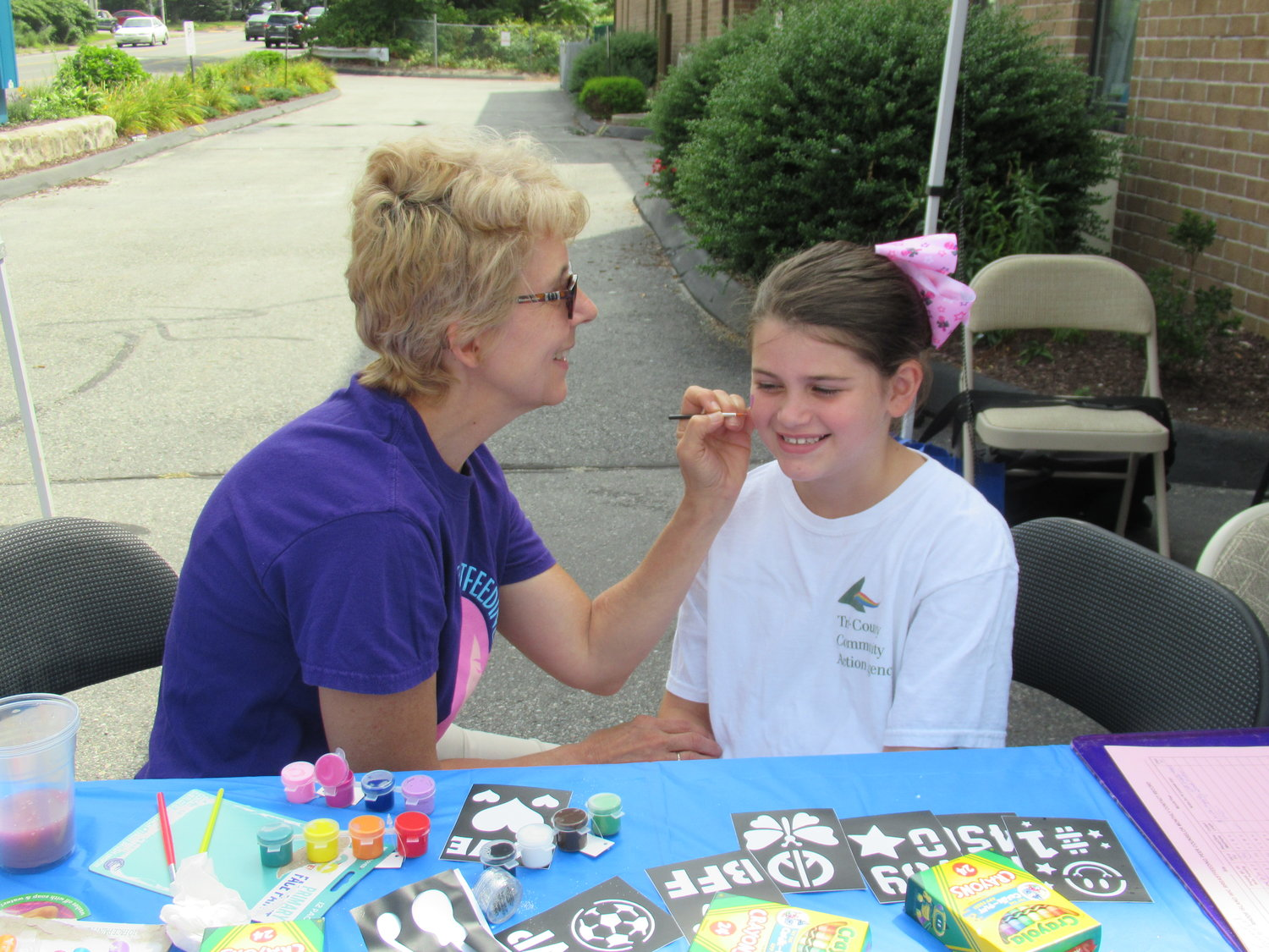 HAPPY HANNAH: Hannah Jackson, 7, enjoys having her face painted by Tri-County Community Action Agency Early Head Start Director Julissa Garo performed during Saturday's first-ever farmers market.